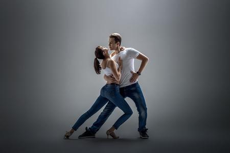 beauty couple dancing social danse ( kizomba or bachata or semba or taraxia) , on grey background Фото со стока - 70224436