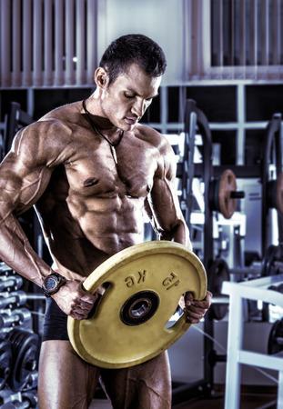 muskeltraining: Bodybuilder Guy, führen Übung mit Gewicht in der Turnhalle, vertikale Foto, blau, violett Ton