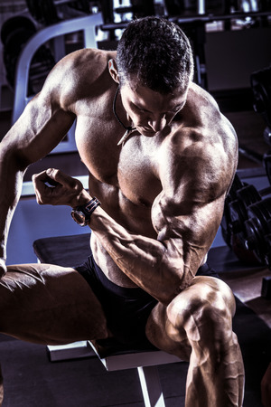 musculation: very power athletic guy ,  execute exercise with  dumbbells, on gym background, blue, violet tone