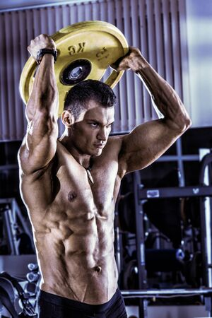 musculation: guy bodybuilder , execute exercise with weight in gym, vertical photo, blue, violet tone Stock Photo