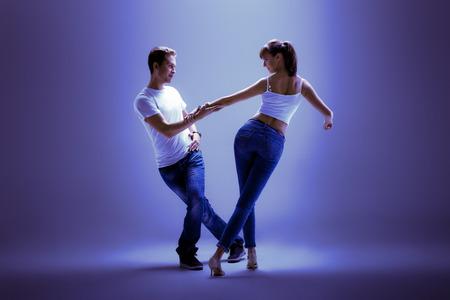 beauty couple dancing social danse ( kizomba or bachata or semba or taraxia) , on blue background, blue, violet tone