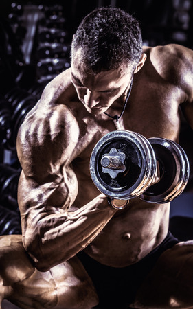 execute: very power athletic guy ,  execute exercise with  dumbbells, on gym background, blue, violet tone
