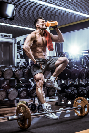 musculation: guy bodybuilder tired sit in gym and drink sportive nutrition - protein of shaker , vertical photo