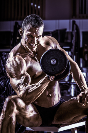 musculoso: very power athletic guy ,  execute exercise with  dumbbells, on gym background, blue, violet tone