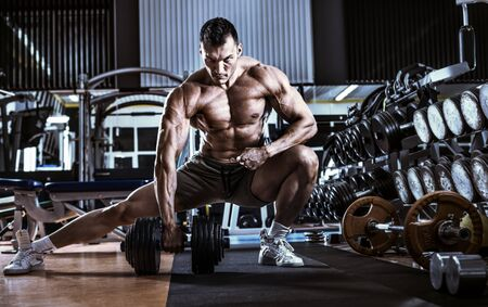 and the horizontal man: bodybuilder man, execute exercise with  dumbbells, inside gym, horizontal photo
