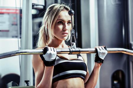 junge Frau Fitness führen Sie Übung mit Übung-Maschine im Fitness-Studio, horizontale Foto
