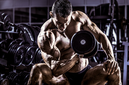execute: very power athletic guy ,  execute exercise with  dumbbells, on gym background, horizontal photo, blue, violet tone