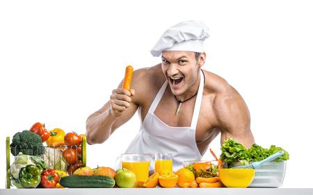 Man Bodybuilder in weiß toque blanche und kochen Schutzschürze, Gebräu Gemüse und Obst, auf weißem Hintergrund, isoliert