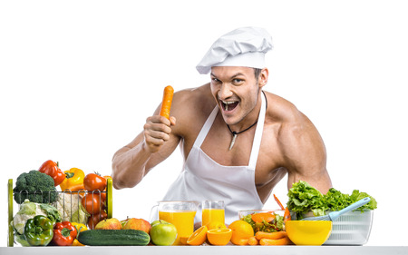 Man bodybuilder in white toque blanche and cook protective apron, concoction vegetables and fruit , on white background, isolated Stock Photo