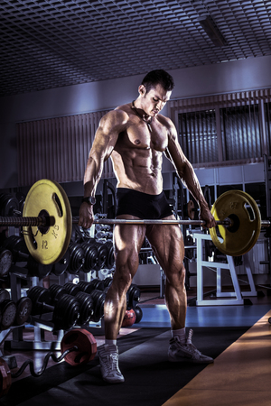 guy bodybuilder , execute exercise with weight in gym, vertical photo, blue, violet tone Stock Photo