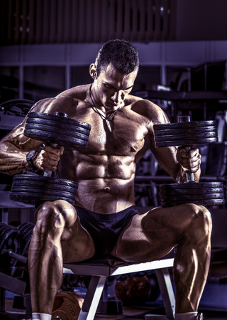 musculation: very power athletic guy bodybuilder , sit with  dumbbells, in dark gym, blue, violet tone Stock Photo