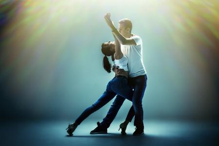 actitud: belleza pareja bailando danza sociales (kizomba o bachata o Semba o taraxia), sobre fondo azul