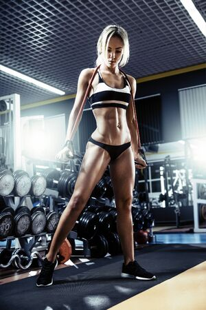 young fitness woman execute exercise with expander in gym, vertical photo