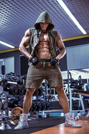 musculation: guy bodybuilder stand in gym, vertical photo