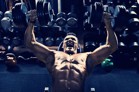 muscle guy: guy bodybuilder, execute exercise press of dumbbells on pectoral muscle, in gym, blue, violet tone