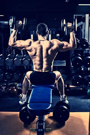 musculation: guy bodybuilder execute exercise with dumbbells, on deltoid muscle shoulder, blue, violet tone