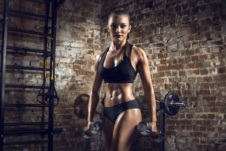 musculation: young fitness woman execute exercise with dumbbells in gym on brick background, horizontal photo Stock Photo