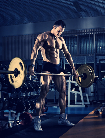 guy bodybuilder, execute exercise with weight in gym, in the standing position, blue, violet tone Stock Photo