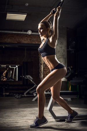 musculation: young fitness woman execute exercise  in gym, vertical photo