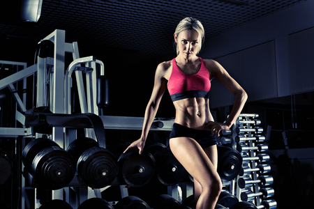 musculation: beautiful girl bodybuilder, execute exercise with weight, blue, violet tone Stock Photo