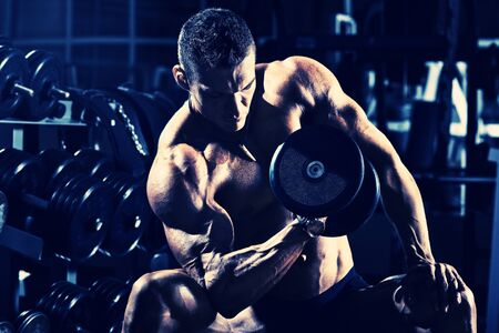 athletics: very power athletic guy bodybuilder ,  execute exercise with  dumbbells, in dark gym, blue; violet tone Stock Photo