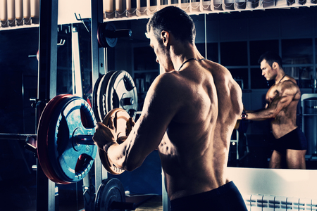 musculation: bodybuilder guy , execute exercise with  weight, in gym, blue; violet tone Stock Photo