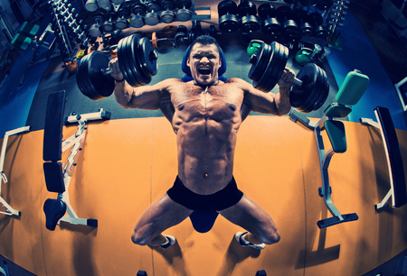 guy bodybuilder execute exercise press of dumbbells on pectoral muscle, in gym Stock Photo