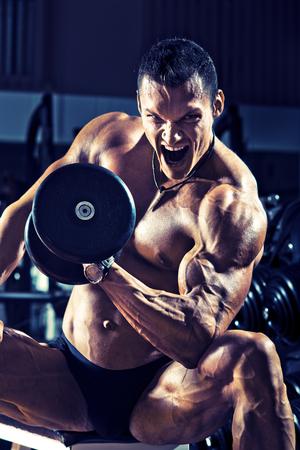 muskeltraining: sehr Power athletic Guy, führen Übung mit Hanteln, auf Gymnastik Hintergrund, blau, violett Ton