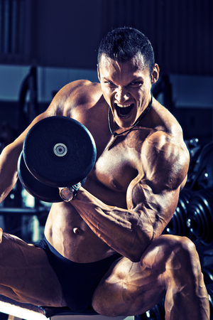 very power athletic guy ,  execute exercise with  dumbbells, on gym background, blue, violet tone