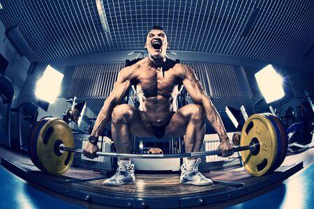 muskeltraining: Guy Bodybuilder führen Übung Kreuzheben mit Gewicht, in Gym, blau, violetten Ton