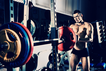 musculation: bodybuilder guy , execute exercise with weight, in gym, blue; violet tone