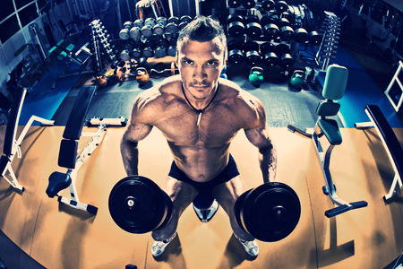 musculation: guy bodybuilder, with dumbbells, in gym Stock Photo