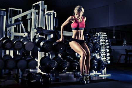 muscle training: Bodybuilder schöne Mädchen, führen Sie Übung mit Gewicht, blau, violett Ton