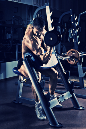 very power athletic guy bodybuilder,  execute exercise with  dumbbells, on Scotts bench, in gym, blue; violet tone Stock Photo