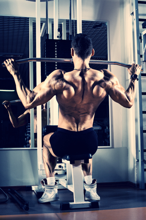 muscle guy: very power athletic guy bodybuilder, execute exercise with gym apparatus, on broadest muscle of back Stock Photo