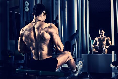 muscle guy: very power athletic guy bodybuilder,  execute exercise with gym apparatus, on broadest muscle of back, blue, violet tone