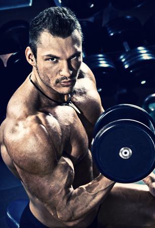 vertical portrait, guy bodybuilder execute exercise with dumbbells, in dark gym, blue, violet tone