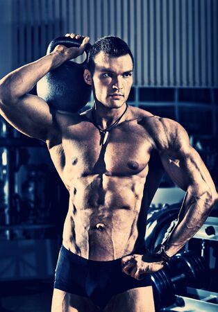 portrait guy - bodybuilder, with weight, in gym, blue, violet tone photo