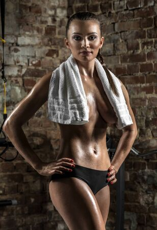 musculation: young fitness woman in gym , in towel on brick background, vertical photo