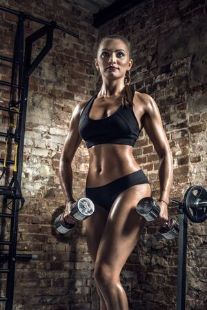 young fitness woman execute exercise with dumbbells in gym on brick background, vertical photo Stock Photo