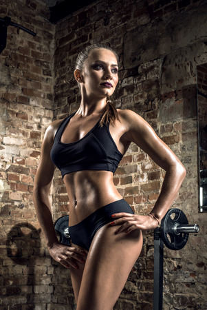 musculation: young fitness woman in gym on brick background, vertical photo