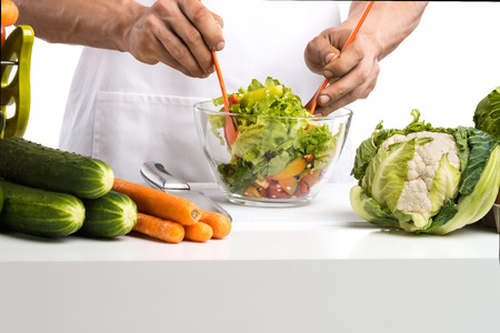 man hand cook make mix vegetables salad on kitchen, closeup photo, on whie background; isolated photo