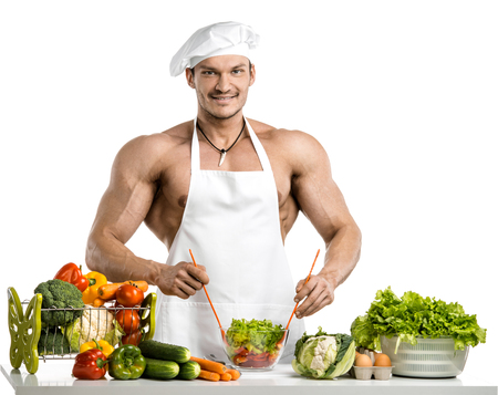 Man bodybuilder in white toque blanche and cook protective apron, concoction vegetables and fruit , on whie background, isolated photo