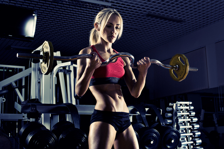 musculation: beautiful girl bodybuilder ,  execute exercise with  weight, in dark gym