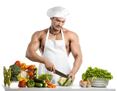 Man bodybuilder in white toque blanche and cook protective apron, concoction vegetables and fruit , on whie background, isolated