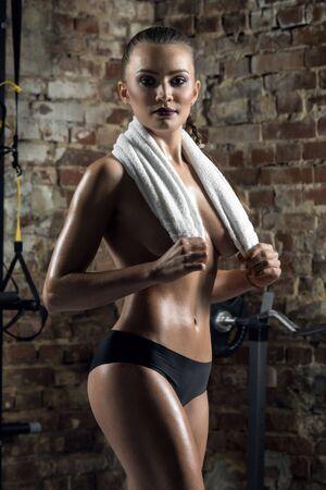 Junge Fitness Frau in Fitness-Studio, in Handtuch auf Backstein Hintergrund, vertikale Foto Standard-Bild