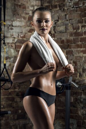 brawny: young fitness woman in gym , in towel on brick background, vertical photo