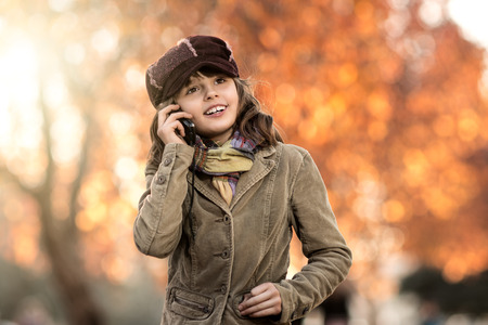 vertical photo, stylish beautiful little girl hold mobile phone and gladness talk photo