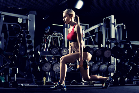 beautiful girl bodybuilder , execute exercise with dumbbells, in dark gym , blue; violet tone