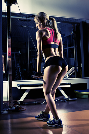 fitness girl, execute exercise with gym apparatus, on triceps, blue, violet tone